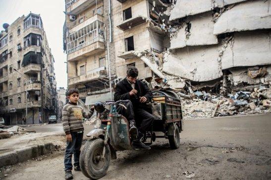 Un padre y un hijo recogen cosas de un edificio abandonado en el centro de Alepo. Miembros de Al-Qaeda se esconden en el área de Bustan al-Qaser donde se enfrentan al ejercito de al-Asad. GETTY IMAGES